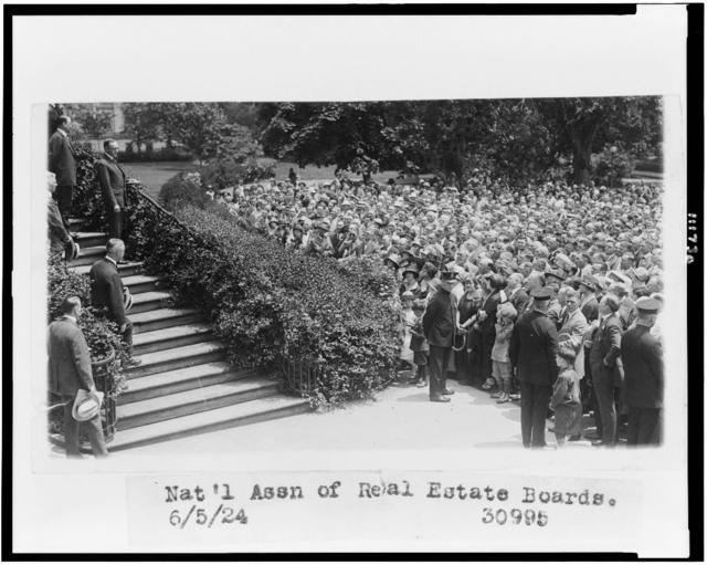 [President Calvin Coolidge, full-length, standing on steps, facing right, in front of crowd of members of the National Association of Real Estate Boards]
