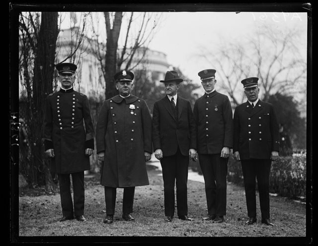President Coolidge personally congratulates the [...] members, one each from the police and fire departments of the District of Columbia who have been decorated with gold medals for conspicuous bravery in the line of duty during 1924. Left to right: Chief of Police Daniel Sullivan, Policeman John F. Mc[...] President Coolidge, Chief George S. Watson of the Fire Depart[...] and Private Pearson Talbott of No. 23 Engine Company [White House, Washington, D.C.]