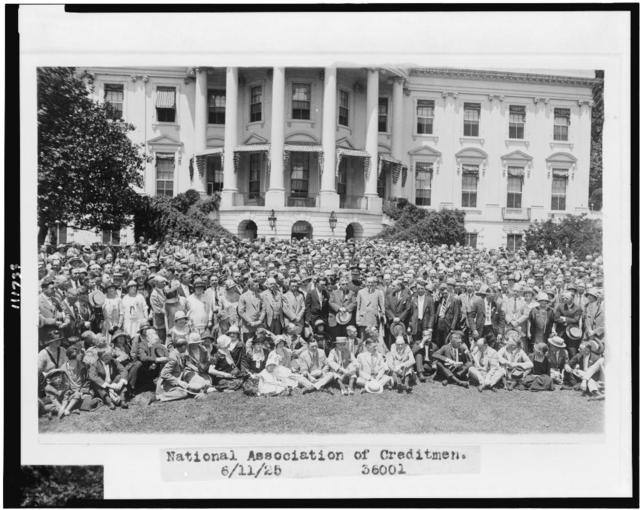 [President Coolidge posed with crowd of members of the National Association of Creditmen, with the White House behind them]