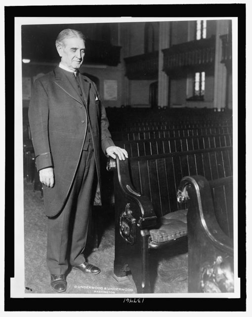 [Rev. James S. Montgomery, full-length portrait, standing by the pew to be occupied by Vice-President Charles Curtis at the Metropolitan Memorial M.E. Church, Washington, D.C.] / Underwood & Underwood, Washington.
