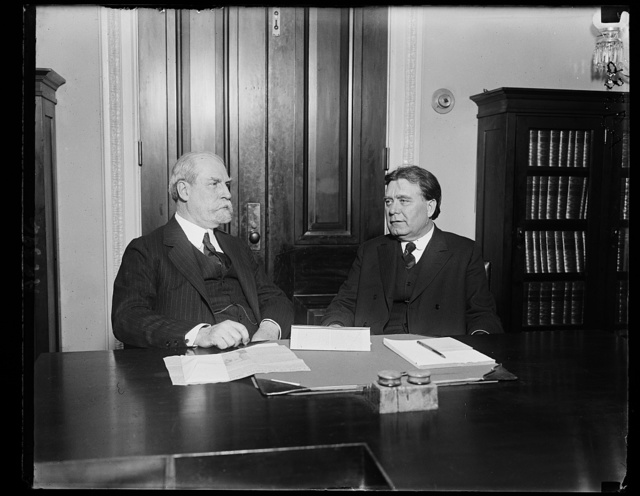Secretary of State Charles Evan Hughes, (left), with Senator Borah, Chairman of the Foreign Relations Committee, leaving a two hour executive session on February 2, when both Secretary Hughes and Secretary Hoover were heard regarding the German Commercial Treaty, intended as a model for conventions with other nations