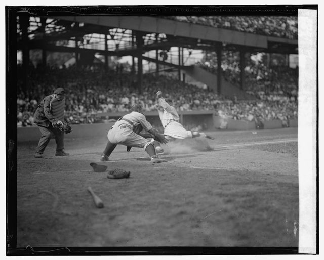 Senators Goose Goslin slides safely into home and collides with Yankees catcher Wally Schang in 2nd game of double header (baseball)