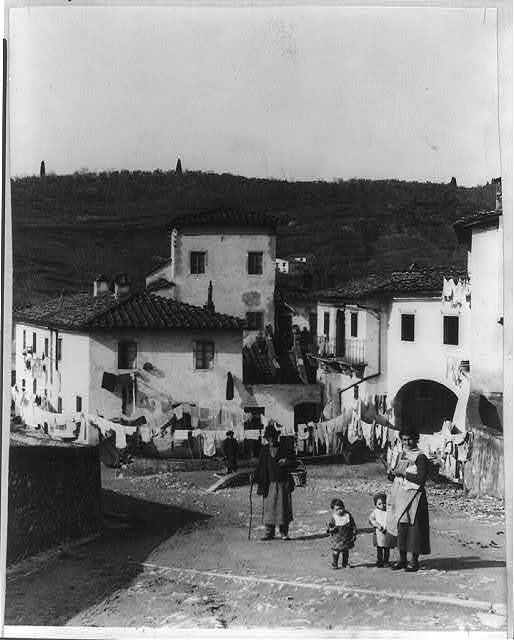 [Small Italian village; woman, 2 small children, and man in foregrd.]