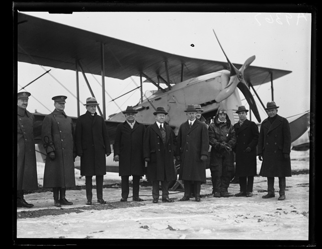 The new amphibian airplane, that is at home both [...] water and land was inspected by a Congressional Committee at Bolling Field, Monday, January 19. The machine was designed by Grover Loenig, of New York. Left to right in the group, standing before the neew plane are: Major H.B. Clagett, Commander of Bolling Field; Representatives Frank Reed, Florian Lampert, Randolph Perkins, A.S. Prall, Major Raycroft Walsh, Lt. Wendell H. Brookley, who piloted the machine from New York to Washington, Mr. Loening, the designer, and Rep. Roy O. Woodruff