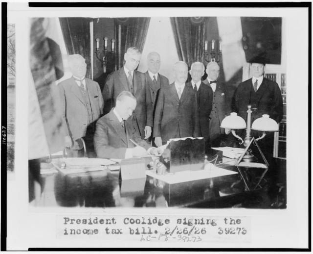 [Calvin Coolidge signing the income tax bill, also known as the Mellon tax bill. Secretary of the Treasury Andrew Mellon is the third figure from the right, and Director of the Budget, General Herbert Mayhew Lord, is to Mellon's left]