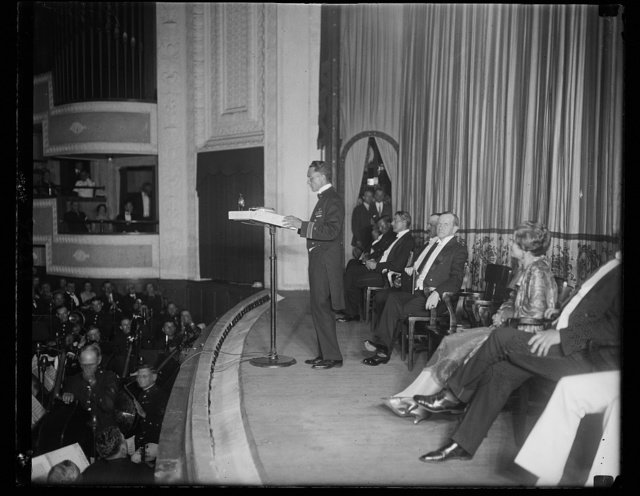Commander Richard E. Byrd, the first man to reach the North Pole by airplane, repeating his experiences on the flight before President and Mrs. Coolidge and an audience of 6,000, including cabinet officers, members of the diplomatic corps. and representatives of National Geographic Society from whom he ? the Hubbard Gold Medal in Washington, June 23rd. The President presented Byrd and his pilot Floyd Bennett with medals. Gift from National Geographic Society
