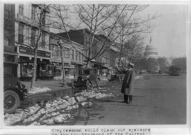 [Congressman John Boylan of New York points at unsightly property on Pennsylvania Ave., with U.S. Capitol in background]