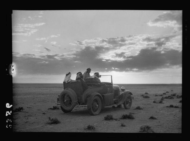 El-Azrak & Wadi Sirhan in the Arabian Desert. Druse [i.e., Druze] political refugees from Jebel Druse (The Hauran). Evening on the desert. Car in desert, silhouetted against striking cloud effect