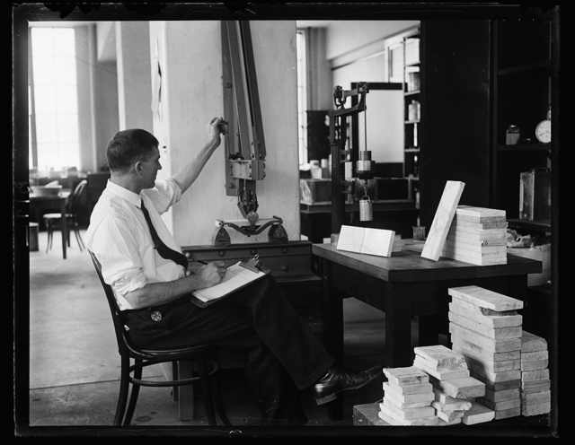 Is marble elastic, you inquire? Yes, tests that the Bureau of Standards show that a specimen of marble when subjected to great pressure stretches or gives a certain degree without breaking. This photograph shows D.W. Keesler conducting the so-called flexture test with a machine while was designed for the purpose