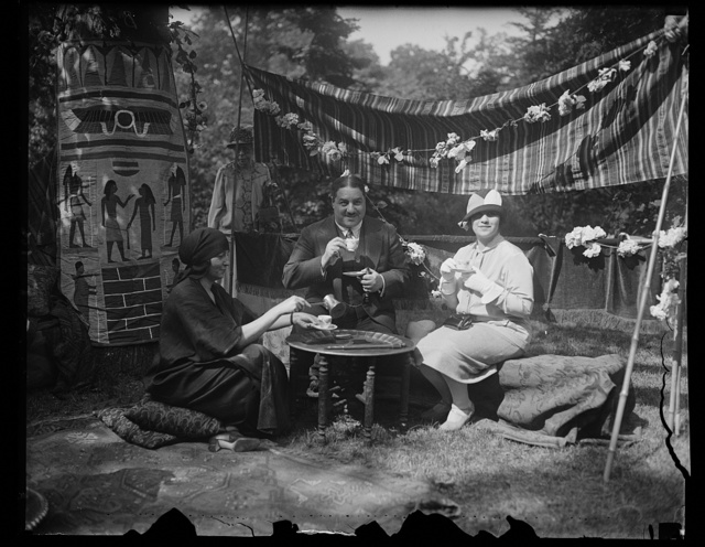Neighborhood house garden fete. The Egyptian Minister and Mme Smay Pasha, (right) refreshing themselves with coffee at the Egyptian booth served by Mrs. R.W. Imbrie. Mrs. Imbre is the widow of Maj. Imbre who lost his life in Persia several years ago