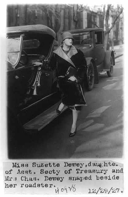Suzette Dewey, daughter of Charles Dewey, posed beside roadster