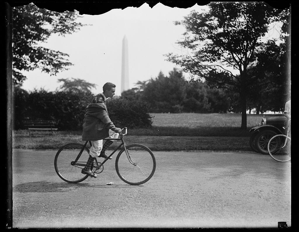 [Bicycle rider;Washington Monument in background, Washington, D.C.]