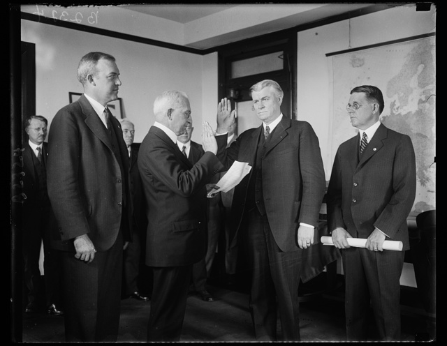 New solicitor for Department of Commerce is sworn in. Ephriam F. Morgan of Charleston, West Virginia, former Governor of the state of West Virginia, being sworn in as solicitor of the United States Department of Commerce to succeed Judge Stephen B. Davis, resigned. In the photograph, left to right: William P. MacCracken, Assistant Secretary of Commerce; E.W. Libbey, Chief Clerk of the Department who administered the oath; Ephriam Morgan and Walter F. Brown, Assistant Secretary of Commerce