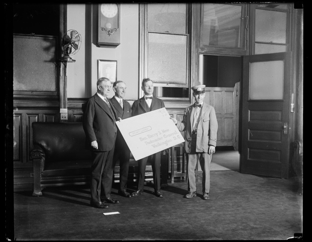 Postmaster General receives largest postcard sent through mails. [...] postcard ever sent through the mails was delivered [...]eneral Harry S. New today as an invitation to [...]ening of the Bicennial Conference of the National [...] Post office clerks in Indianapolis, Ind., Sept. 5. [...]red 24 by 36 inches and required one dollar in postage. Left to right: Postmaster General New; Thomas F. [...] retary National Federation of Postoffice Clerks; President of the federation and G.K. Mulvey, carrier [...] the card