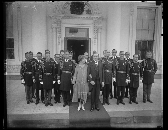 Pres. and Mrs. Coolidge with the military and Naval White House aides of the New Year's Reception. Right back of Pres. is Col. Sherwood Cheney, Chief Military Aide; Commander Wilson Brown, Chief Naval Aide is behind Mrs. Coolidge
