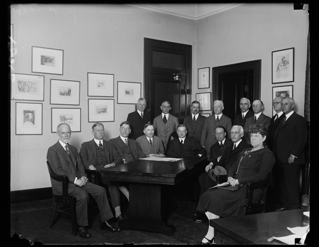 President appoints committee of four cabinet members to cooperate with Red Cross in aiding flood sufferers. After making an appeal to the people of the country today for prompt and generous contributions to the American Red Cross relief fund for sufferers in the flood area of the Mississippi river, President Coolidge appointed a committee of four cabinet members to cooperate with the officers of the Red Cross in their relief work. The cabinet members met with Red Cross Officials today in Washington to determine how the Federal Government through its many agencies can best cooperate. In the photograph, left to right; (sitting) Rear Admiral E.R. Stitt, chief of U.S. Navy Bureau of Medicine and Surgery; Secretary of War, Dwight F. Davis; Secretary of the Navy, Curtis D. Wilbur; James L. Feiser, Acting Chairman of the Red Cross; Secretary of Commerce, Herbert Hoover; Assistant Secretary of the Treasury, Charles S. Dewey; Secretary of the Treasury, Andrew Mellon and Miss [...]