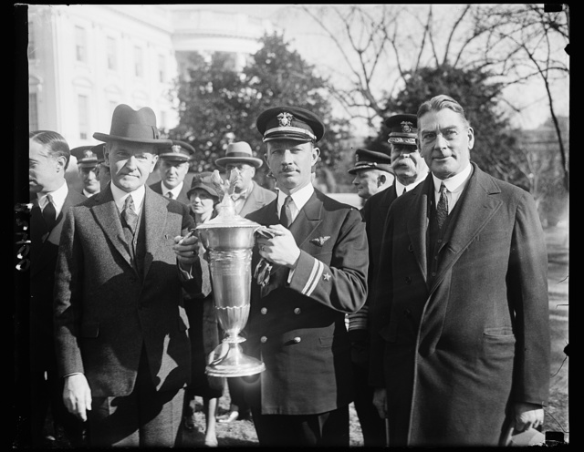 President Coolidge presents flying trophy to U.S. Navy Aviator, President Coolidge presenting the Herbert Schiff Trophy to Lieut. Arthur Gavin, United States Navy at the White House today. The trophy is awarded to naval aviator attaining the greater number in the air without accident during the fiscal [...] goes to Lieut. Gavin this year because of his [...] 865 flying hours, which exceeds two previous [...] 282 and 26 hours, respectively. On the right, Secretary of the Navy, Curtis D. Wilbur