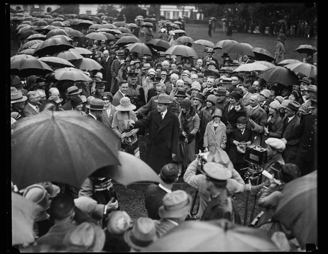 President receives doctors in rain. Braving the wind and rain and against his physician's orders, President Coolidge greeted thousands of doctors at the White House today. The physicians are in Washington attending the annual [...] Convention of the American Medical Association. In this photograph [...]resident Coolidge can be seen in center of group