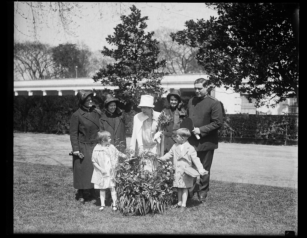 """[Salvation Army children of California send Mrs. Coolidge a gift of flowers by airplane. A beautiful basket of flowers sent by airplane by the children of the Salvation Army Home at Lytton Springs, California, was presented to Mrs. Coolidge at the White House today. Ketha Holtz, daughter of Staff-Captain Ernest R. Holtz, Potomac Divisional Commander of the Salvation Army in Washington and Robert Rose, son of Ensign Robert Rose of Salvation Army, are shown making the presentation which also included a message reading: """"Dear Mrs Coolidge: We are sending you these flowers because we love you""""]"""