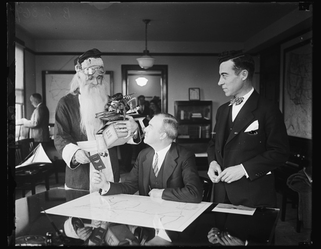 Santa Claus receives aeroplane pilot's license from Assistant Secretary of Commerce. Although there may not be sufficient snow for his reindeer sleigh, Santa Claus will still be able to deliver his load of presents on time this Christmas by using the air route. The old saint called at the Commerce Department in Washington today where he is shown receiving an aeroplane pilot's license from Assistant Secretary of Commerce. for Aeronautics William P. MacCracken, while Clarence M. Young (right) Director of Aeronautics, Department of Commerce, looks on. Airway maps and the assurance that the lights would be burning on the airways Christmas Eve were also given to Santa