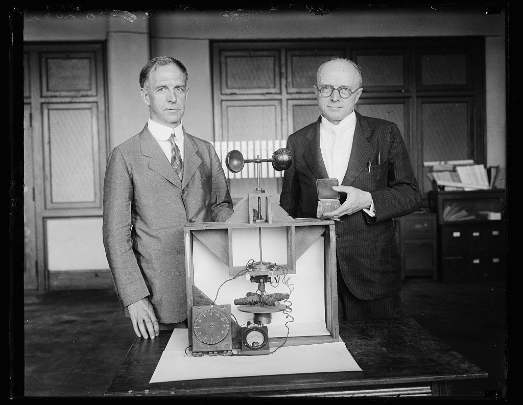 Scientists for Uncle Sam awarded Magellan Gold Medal. Dr. L.J. Briggs, left, Assistant Director and Dr. Paul R. [Heyl?], Chief of the Sound Section of the United States Bureau of Standards, with the first successful experimental model of the earth inductor compass, which they developed for the Army Air Corps and for which they were awarded the Magellan Gold Medal by the American Philosophical Society. It was a model of this same compass that Capt. Charles Lindbergh used on his epochal flight from New York to Paris