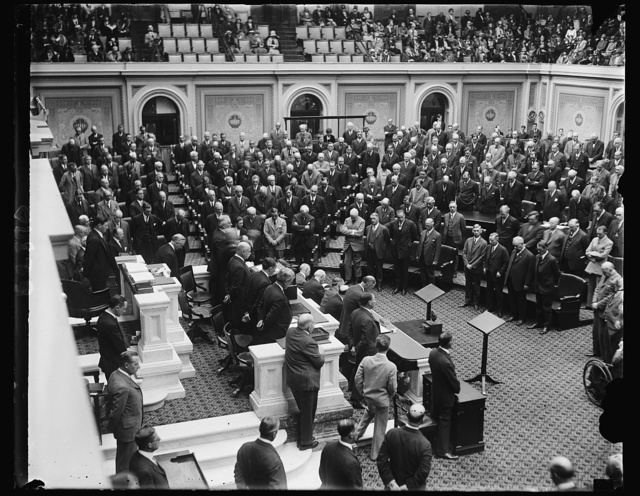 The Seventieth Congress convenes. The Seventieth Congress met at noon today ready to take up tax reduction, farm relief, flood control and many other problems of the nation. Dr. Shera Montgomery, chaplain of the House is shown delivering the opening prayer