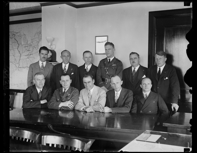 This may help the weather reports. These transoceanic flyers, meeting in Washington with officials of the U.S. Weather Bureau and the Department of Commerce. the Meteorology Committee of the Guggenheim Foundation and representatives of other aeronautical interests, hope to help in improving weather service for aviators. Left to right, seated: Assistant Secretary of Commerce for Aeronautics William P. McCracken, Jr. , Lt. A.F. Hagenberger, Col. Arthur C. Goebel, Paul Schluter, Charles Levine, left to right, standing: Emory Bronte, Edward F. Schlee, Clarence Chamberlain, Lt. Lester J. Maitland, William S. Brock, and Berndt Balchen