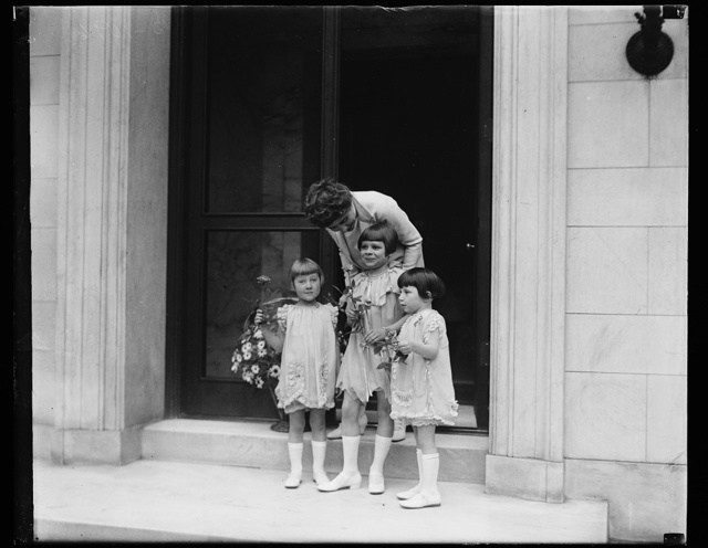 "Washington youngsters surprise Mrs. Coolidge with May Day basket of flowers. [...] the First Lady of the land opened the door of [...] morning she found a May Basket of flowers ha[...] nob. The basket, filled with daisies, was pu[...] little Washington children to tell Mrs Coolidge [...] is Child Health Day."" The daisies represen[...] ""Better Health for Children"" movement. The [...]ph are Nan Norton, Elizabeth Ann Taylor and [...] Cooley"