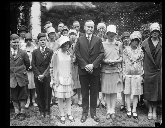 Winners in National Spelling Bee received by President Coolidge. School children from all over the cou[...] who competed in the fourth annual National Spelling Bee held in Washington, were rece[...] by President Coolidge at the White House today. The winners are shown in the center of the group with the President. Reading left to right: Bessie Doig of Detroit, winner of the third award of $200; President Coolidge; Betty Robinson of South Bend, Indiana, the winner of the first prize of $1,000; and Pauline Gray, representing Akron, Ohio, winner of the second prize of $500
