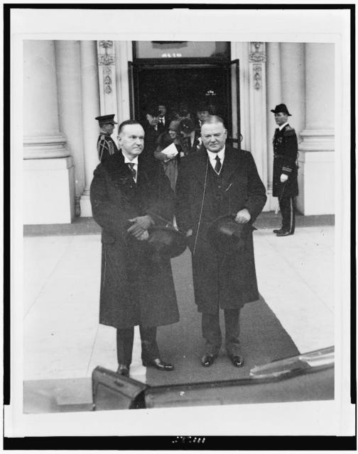 [Calvin Coolidge and Herbert Hoover, full-length portraits, standing, wearing overcoats and holding top hats]