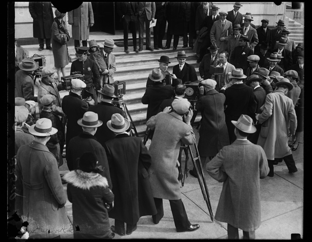 Cameramen charge John D. Rockefeller, Jr., as he leaves U.S. Capitol. John D. Rockefeller, Jr., facing a battery of cameramen at the Capitol in Washington today after testifying before the Senate Public Lands Committee investigating the Teapot Dome leases