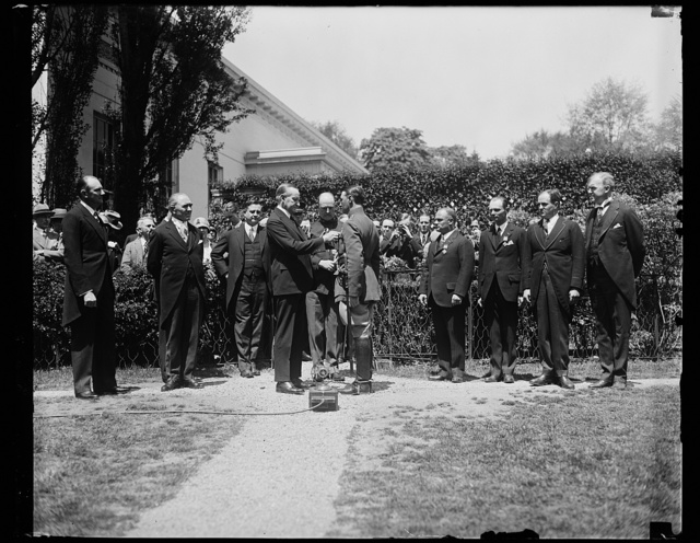Capt. Koehl receives Medal. President Coolidge pinning the Distinguished Flying Cross on the breast of Cap. Koehl, at the White House at noon, May 2. In the group, left to right: Sanders, President Coolidge, Capt. Koehl, Baron Huenefeld, Major Fitzmaurice, Assistant Secretary of War Davison and Assistant Secretary of Commerce MacCracken