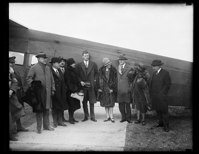 [Charles Lindbergh and group next to airplane]