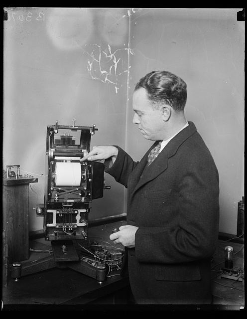 Colored radio recorder is latest in radio receivers. E.B. Judson of the Bureau of Standards and his two colored radio recorder, automatically recording signals in two colors, red and black. This automatic receiver is capable of receiving signals from American or European stations