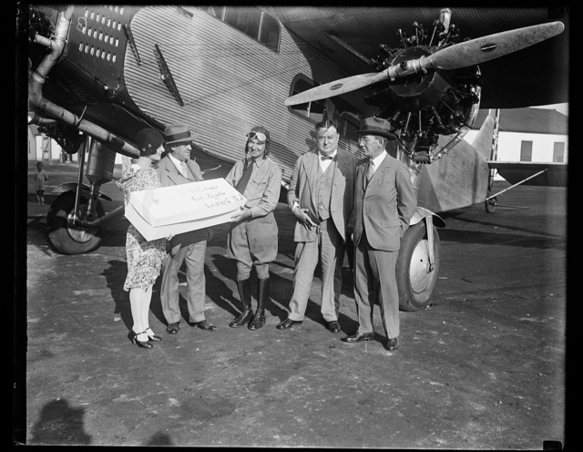 """[Group next to airplane with package addressed to """"Dr. Hugo Eckener, Graf-Zeppelin, Lakehurst, N.J.]"""