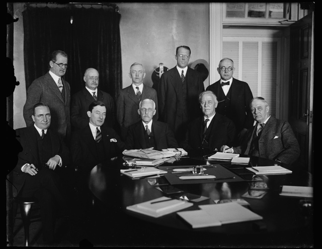 """Mayor Walker of New York confers with Secretary Mellon and other members of Coolidge Cabinet. """"Jimmie"""" Walker, the dapper Mayor of New York City, arrived in the National Capital today and immediately went into conference with Secretary of the Treasury Mellon and Postmaster General New and other high government officials regarding the proposed Federal appropriations for a new Federal court building in New York City and the removal of the present postoffice to a new site in the Metropolis. In the photograph, left to right: (sitting) Undersecretary of the Treasury Ogden L. Mills; Major Walker; Secretary Mellon; Attorney General Sargent; and Postmaster Joseph Johnson, New York City commissioner of Public Works; James A. Wetmore, acting supervising architect of the Treasury; Paul Block, newspaper publisher; Assistant Secretary of the Treasury Carl T. Schuneman; and First Assistant Postmaster General John H. Bartlett"""