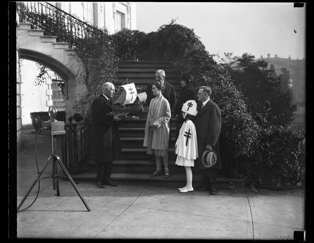 Mrs. Coolidge is presented with original ship model for the 1928 Xmas seals. The original ship model for the 1928 Christmas seals being presented to Mrs. Calvin Coolidge at the White House today by Dr. Kendall Emerson, managinng director of the National Tuberculosis Association. Little Health Crusader Jacquelyn Krah (also shown in the picture) presented Mrs. Coolidge with a supply of Christmas Seals. Others in the photograph are Dr. H.E. Kleinschmidt; Dr. George Kober, president of the Washington Tuberculosis Association; and Mrs. Ernest R. Grant