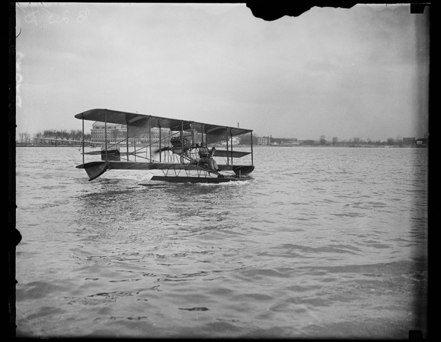 Navy flyer takes 12-year seaplane on its first flight. After lying in storage at the Washington Navy Yard more than 12 years, an obsolete 1915 model Curtiss seaplane on its maiden flight today on the [...] by Commander H.C. Richardson, crack U.S. Navy [...] who is shown at the controls in this photograph. Commander Richardson is planning to put through various tests to compare its behavior to that craft of modern construction for the benefit of Naval officials. The United States Army War College shown in background