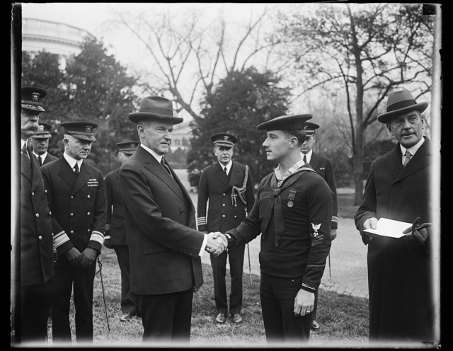 President Coolidge congratulates sailor after presenting him with Congressional Medal of Honor. President Coolidge congratulating William R. Huber, Machinist Mate, First Class, United States Navy, after presenting the sailor with the Congressional Medal of Honor at the White House today Huber was awarded the medal for heroism he displayed aboard the U.S.S. Bruce when an explosion occurred . He rescued shipmates and then at the risk of his life closed off the steampipes
