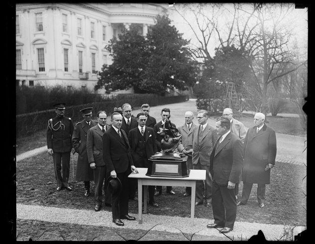 President Coolidge presents Collier Trophy to New York man for most outstanding achievement in aviation for 1927. The much coveted Collier Trophy which is awarded annually for the most outstanding achievement in aviation was presented to Charles L. Lawrence of New York by President Coolidge at the White House today. Mr. Lawrence is the builder and designer of the famous whirlwind motors and was awarded the Trophy for 1927 for his development of them. President Coolidge is on the left in the photograph and Mr Lawrence on the right. Army and Navy Air Corps officials are shown in the background