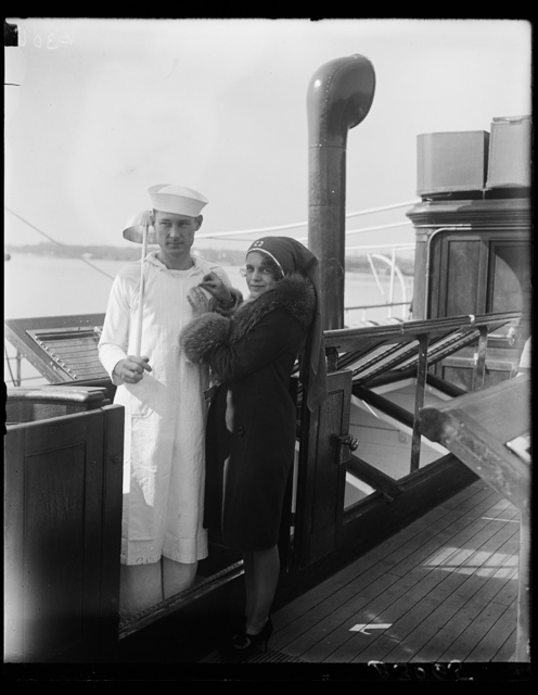 Pretty Washington debutante enrolls cook of Presidental Yacht Mayflower in Red Cross. A group of Washington debutantes took charge of the Presidential Yacht Mayflower today to enroll members of the crew in the Red Cross for 1929, Miss Ann Robbins, daughter of the Assistant Secretary of War, enrolls Tom Cates, the cook amid the cheering of his mates
