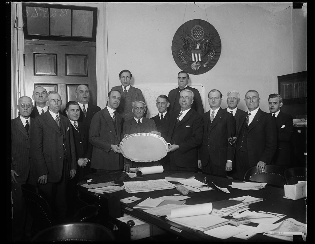 Rep. Lister Hill of Alabama (left) who was married to Miss Henrietta McCormick of Eufaula, Alabama, on February 20th, being presented with a silver service tray by Rep. John J. McSwain of South Carolina, on behalf of the members of the House Military Affairs Committee who are shown in the photograph. Rep. Hill is a member of the Committee