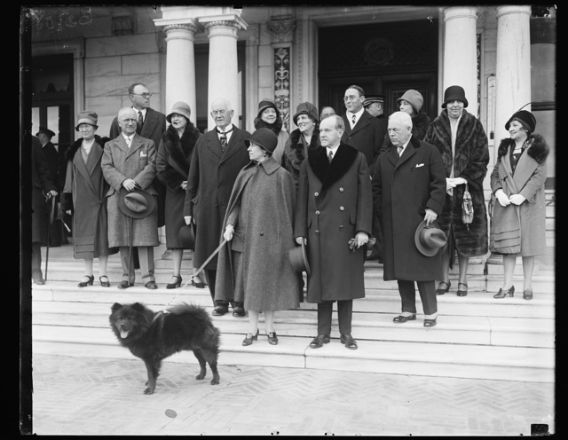 [...] (s) Chief Executive absent for Thanksgiving day. President and Mrs. Coolidge were absent from the White House for this year's observence of Thanksgiving. They journeyed to the Swannaoa Club, near Charlottesville, Va. This picture was made on the steps of the country club. On the left of the President is E.M. Crutchfield, President of the club