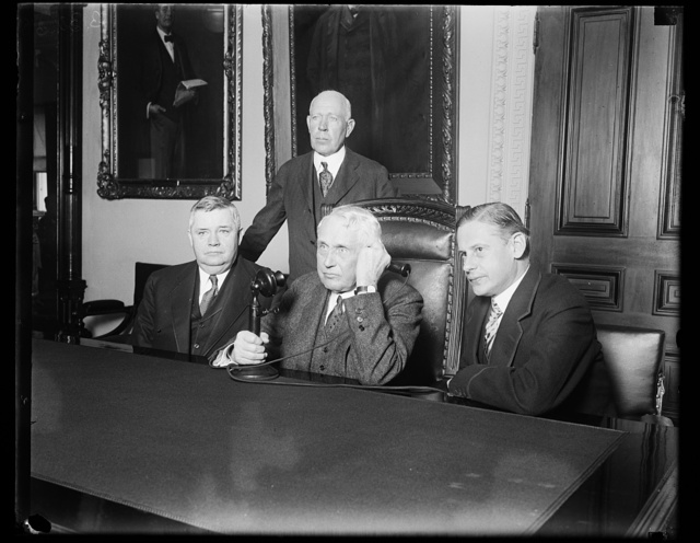 Telephone communication to Austria from United States is established. Telephone communication between the United States and Austria was inaugurated today when the Secretary of State Frank B. Kellogg talked to the American Minister in Vienna Albert Henry Washb[...] and high Austrian officials. In the photograph, left to right, (sitting) J. Ruben Clark, Assistant Secretary of State; Secretar[...] of State Frank B. Kellogg; and the Austrian Minister Edgar Prochnik. Charles G. Clagt[...] General Manager of the Chesapeake and P[...] Telephone Company is standing