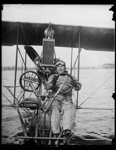 """The good old days of aviation."" Commander H.C. Richardson, crack U.S. Navy flyer, at the controls of a 1915 model Curtiss seaplane which he took on its maiden flight today on the Potomac at Washington. The old plane was discovered in storage at the Washington Navy Yard where it has been for over 12 years. Commander Richardson is testing the old boat to compare its behavior to that of craft of modern construction"