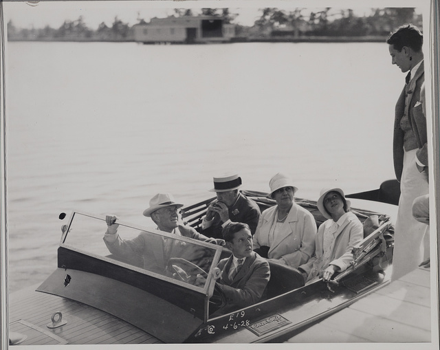 [Thomas Edison and Harvey Firestone sitting in a speed boat at the docks with unidentified individuals]