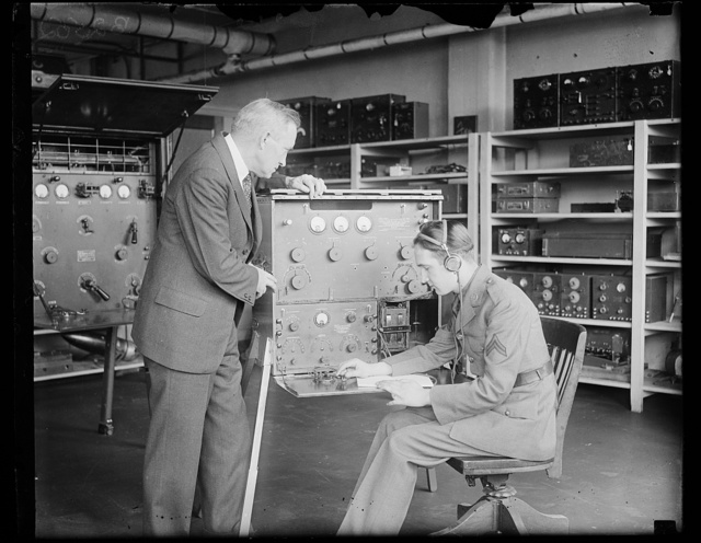 U.S. Chief Signal Officer inspects new radio equipment for talking to Aviators in flight. The new aircraft-radio equipment designed by both the Signal Corps of the War Department permits of both radiotelephone and radiotelegraph communication, sending, receiving, at the same time. The apparatus is used communicating with airplanes in flight. Corporal [...] is demonstrating the outfit to the Chief Signal Officer, Major General George S. Gibbs, this is the first photograph showing him with radio