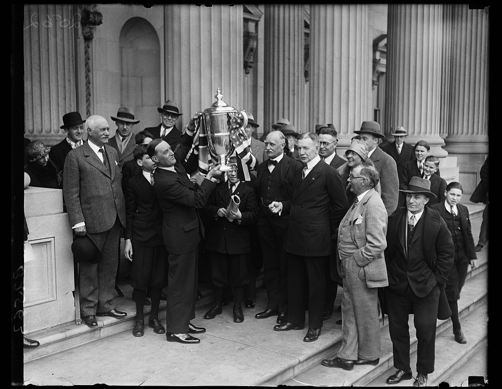 Vice President Dawes presents silver trophy to British Army Officer for establishing new racing automobile record. Capt Malcom Campbell who established a new world's automobile racing record when he drove his Napier Bluebird Special at the rate of 205.9 miles today in Florida recently, received the Daytona Beach silver trophy for his daring feat from Vice President Charles G. Dawes at the Capitol in Washington today. In the photograph, left to right: United States Senator Duncan U. Fletcher of Florida; Capt. Campbell holding the cup; Sir Esme Howard, British Ambassador; Vice President Dawes; and Eugene Pullian, publisher of Daytona Beach Journal