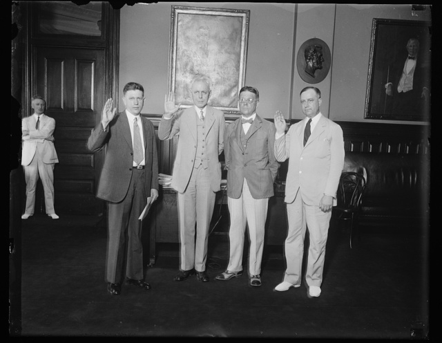 Administrative Assistant to Postmaster General and Assistant Postmaster General take oath of office at same time., Robert S. of Lancaster, Pa., beings sworn in as Administrative Assistant to Postmaster General Brown, and Frederic A. Tilton of Detroit, Mich., taking the oath of office as Thrid Assistant Postmaster General today. In the photograph, left to right: A.E. Davis, Chief Clerk of Post Office Department, who administered the oaths; Frederic A. Tilten; Walter S. Brown; Postmaster General; and Robert S. Regar