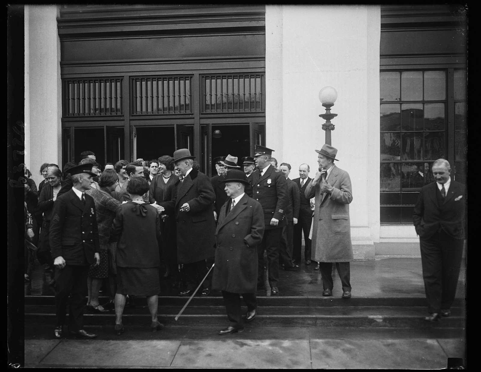 Al Smith is given warm greeting by Navy ... when he calls on Secretary of Navy Adams. Work was practically at a standstill today at the Navy Department in Washington when former Governor Al Smith called on Secretary of the Navy Charles Francis Adams, asking the advice of Navy Engineers in the construction of mooring mast on new Empire State Building in New York. The Happy Warrior is shown besieged by admirers as he left the Navy Building after the conference with the secretary. In the right foreground (with derby) is William F. Kenney, who accompanied former Governor Smith to Washington